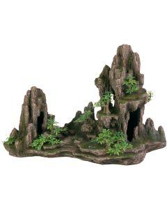 Stor klippformation med flera grottor och växter
